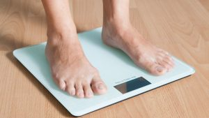 Person standing bare-footed on a bathroom scale