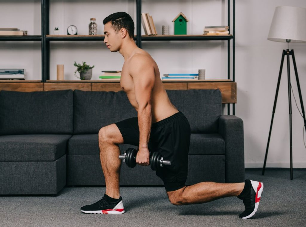 Fit man working out at home doing lunges with dumbbells